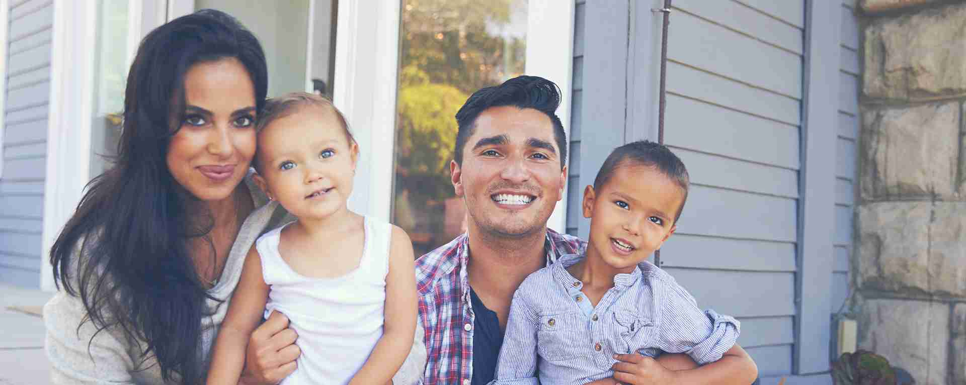Two young foster parents with their little boy and girl